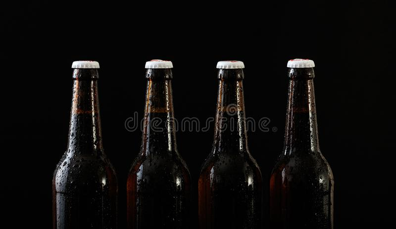Closeup of four beer bottles isolated on black background stock illustration
