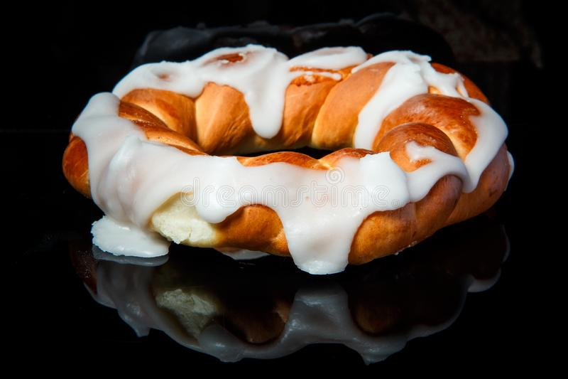 Closeup fresh baked bun with white caramel decoration. Served on mirror black background stock photo