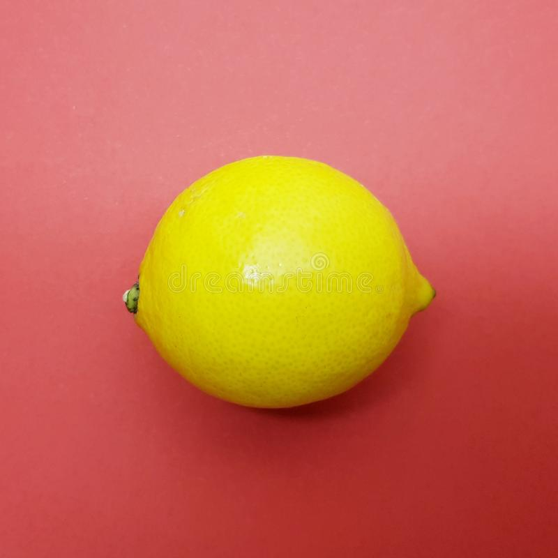 Yellow delicious lemon over red background. Healthy lemons. stock image