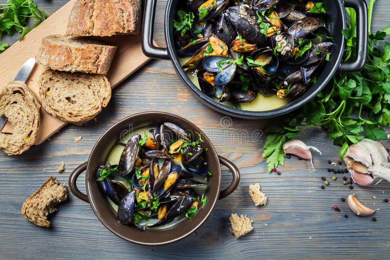 Closeup of fresh garlic and parsley to prepare mussels stock images