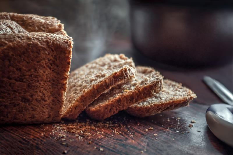 Closeup of fresh homemade organic whole grain bread with crispy crust and warm steam cut into slices stock photography