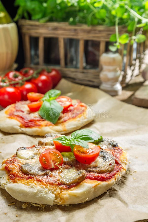 Closeup of fresh ingredients for a mini pizza with mushrooms stock images