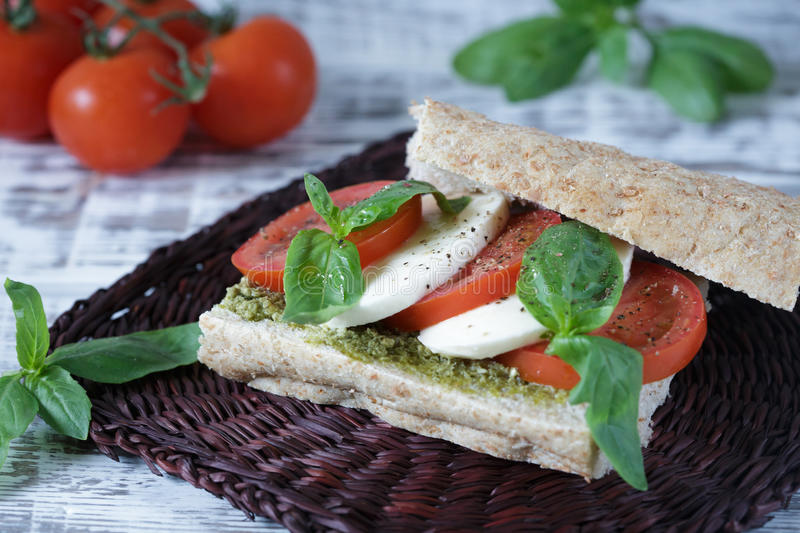 Closeup of a fresh sandwich with mozzarella, tomatoes, pesto. And basil. Sandwich Caprese. Selective focus royalty free stock photos