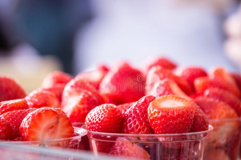 Closeup Fresh Strawberries with tops sliced off and in plastic cups displayed at the amrked-room for text stock photography