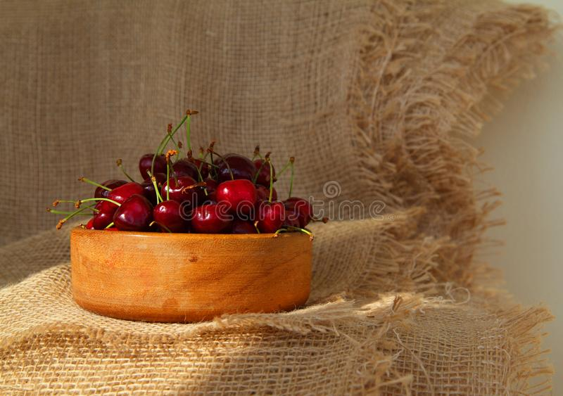 Closeup of fresh tasty cherries in wooden bowl. Rustic style dessert royalty free stock photography