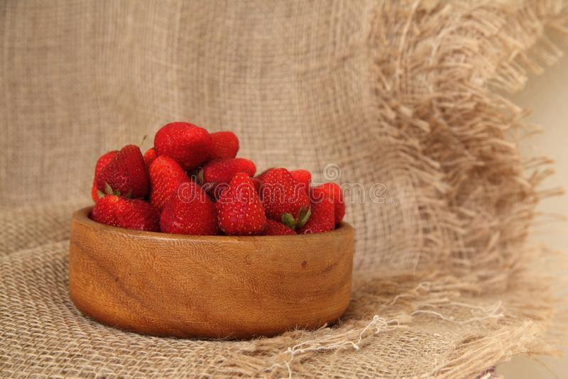 Closeup of fresh tasty strawberries in wooden bowl. Rustic style dessert royalty free stock image