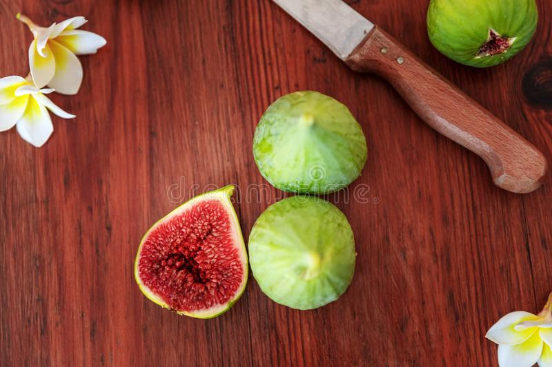 Closeup Fresh whole and cut fruits figs and exotic plumeria flowers on wooden table background with kitchen knife. Still royalty free stock photography