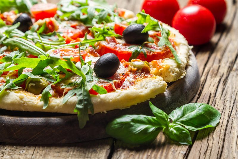 Closeup of freshly baked pizza with basil and tomatoes royalty free stock images