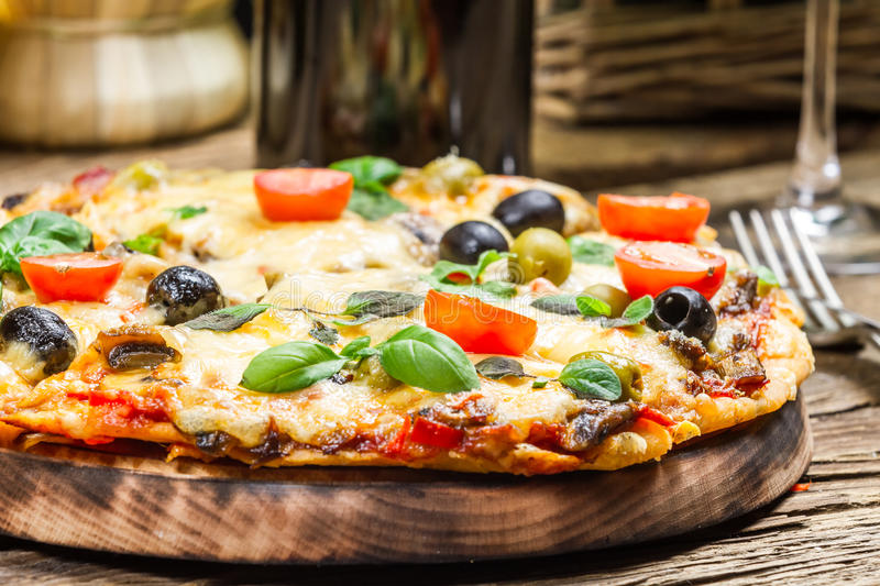 Closeup of freshly baked pizza served with wine royalty free stock photo