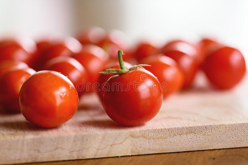 Closeup of fresh homegrown cherry tomatoes on a wooden cutting board royalty free stock photography
