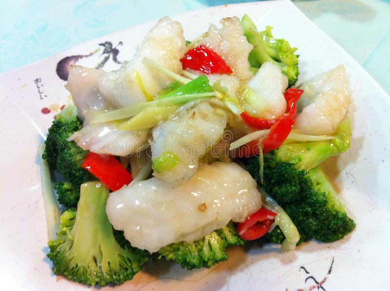 Closeup of fried broccoli with sliced fish fillet, chinese chive and red chili royalty free stock photos