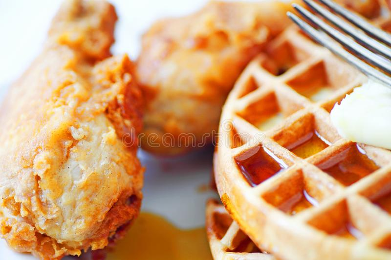 Fried chicken legs with Belgian waffles. Closeup of fried chicken legs, Belgian waffles, butter and maple syrup with a fork stock photography