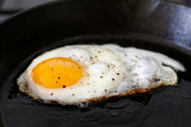Closeup of fried egg in cast iron frying pan sprinkled with ground black pepper. royalty free stock photos
