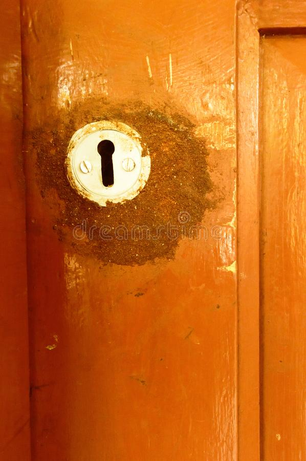 Closeup front view exterior old rusty rough brown wooden door keyhole of iron metal frame with in grungy style and good texture of stock photo