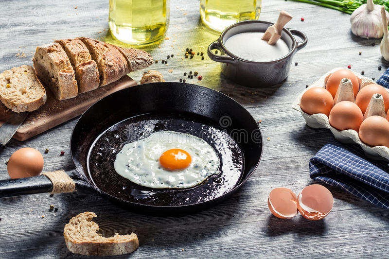 Closeup of frying eggs and fresh bread stock photos