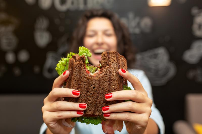 Closeup funny blurred protrait of young woman hold bitten sandwich by her two hands. Sandwich in focus. dark background royalty free stock images