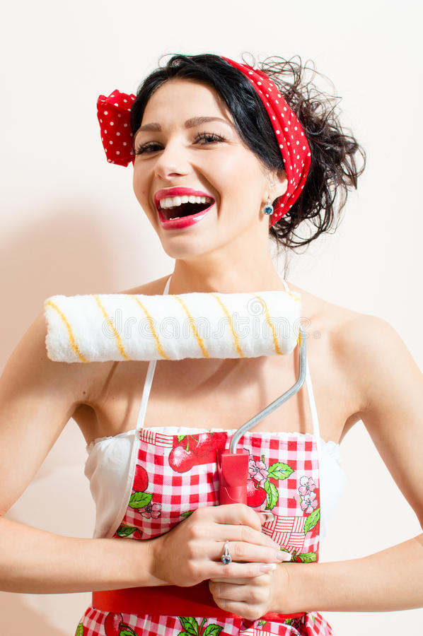 Closeup on funny brunette pinup pretty girl holding paint bolster, having good time & fun looking at camera and laughing. Picture of beautiful funny brunette royalty free stock photography