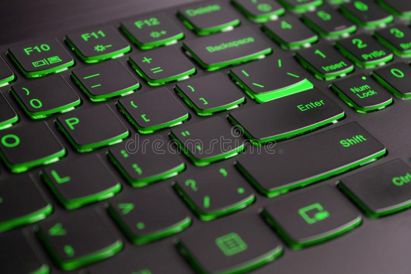 Closeup of gamer laptop keyboard green illumination, backlit keyboard, english letters royalty free stock images