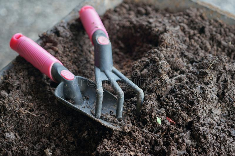 Closeup gardening tools on the fertile soil. Leisure activity in organic farming stock photography