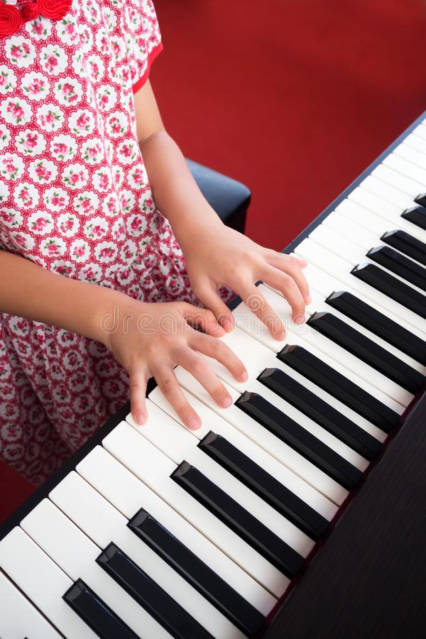 Closeup girl hand playing piano. Favorite music for learning to basic of music and rhythm skill. royalty free stock photography