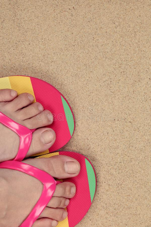 Closeup of a girl's feet wearing flip flops. Closeup of a girl's feet wearing flip flops on sand beach background royalty free stock image