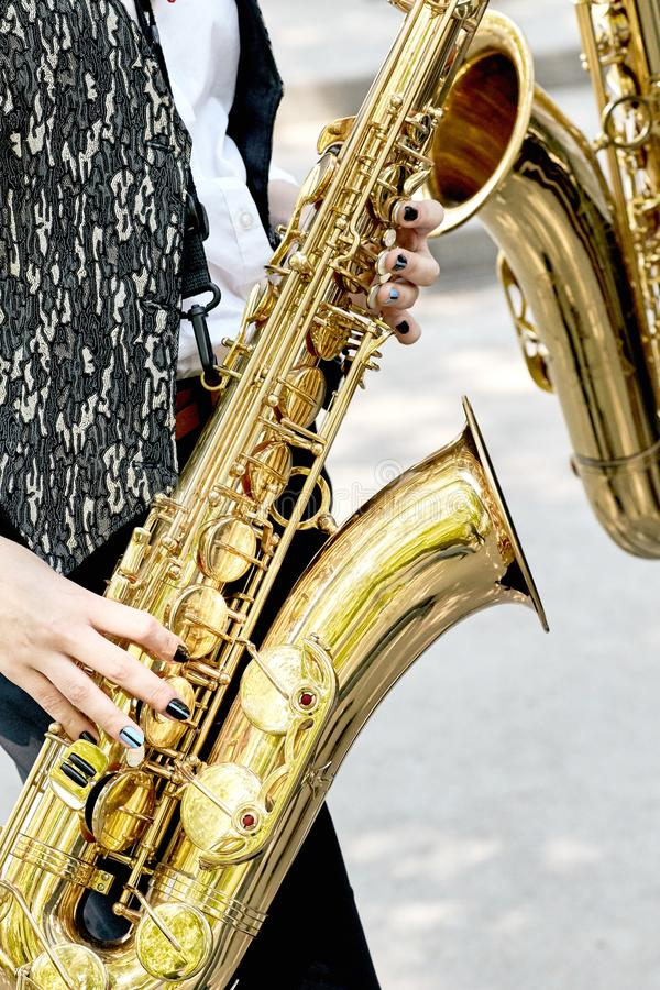 Closeup of a girl with two beautiful gold saxophone in the park. royalty free stock image