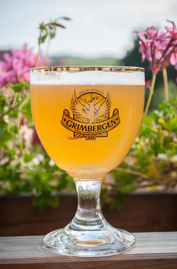Closeup of glass of Alsatian beer from Grimbergen brand at restaurant terrace stock image