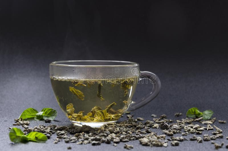 Closeup of fresh made green tea with mint leaves. Closeup of glass cup of hot green tea with mint flavor, dark background Refreshing green tea with mint leaves royalty free stock photo