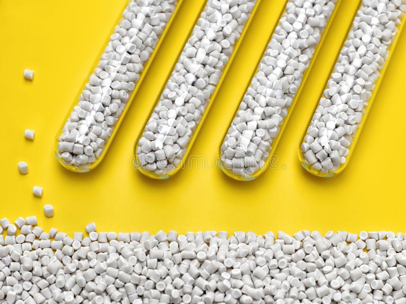 Closeup of glass flasks with granules of chalky polymer. On a bright yellow background royalty free stock photography