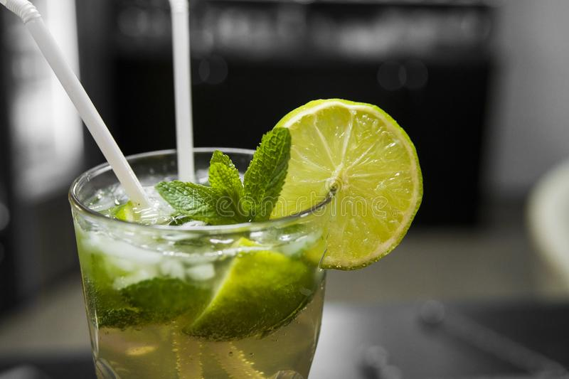 Closeup glass of unalcohol mohito cocktail with lime and mint decorated with slice of lime and with a two tubes at bar royalty free stock photography