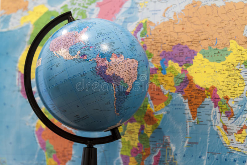Closeup of a globe with asia and africa and a world map with nor. Th and south america on the wall in classroom royalty free stock image