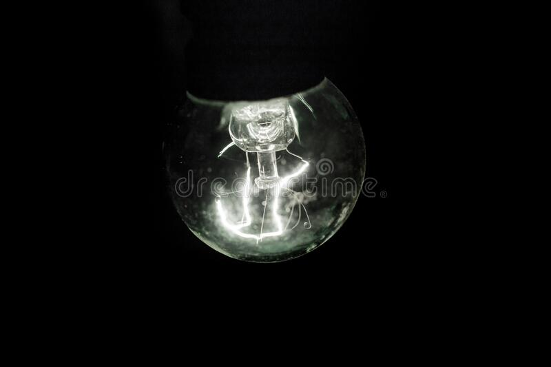 A retro light bulb glowing in black dark background. Side view royalty free stock photo