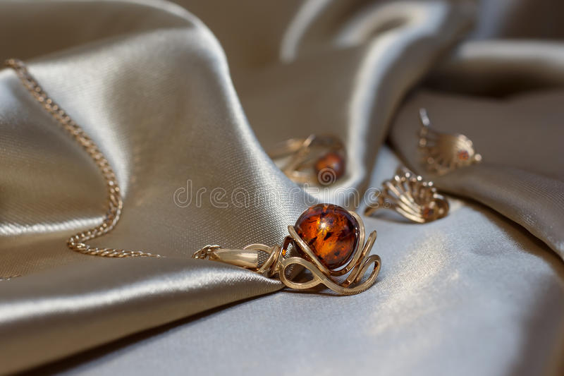 Closeup gold chain with pendant from gold and authentic baltic amber on light brown atlas. royalty free stock photo