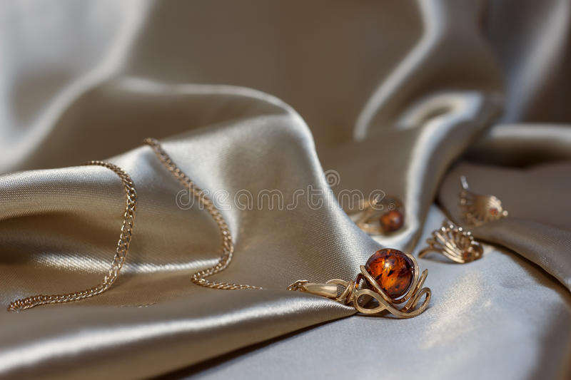 Closeup gold chain with pendant from gold and authentic baltic amber on light brown atlas. Gold earrings and ring with amber. royalty free stock images