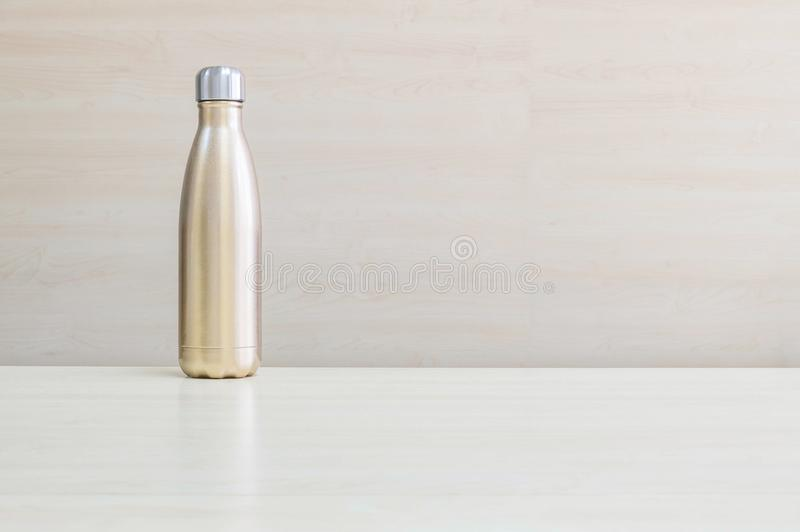 Closeup gold color of aluminium flask for keep hot water on blurred wooden desk and wall textured background under window light royalty free stock image
