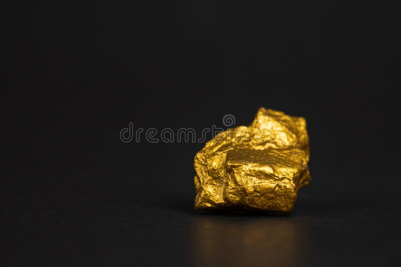 Closeup of gold nugget or gold ore on black background, precious. Stone or lump of golden stone, financial and business concept idea royalty free stock photo