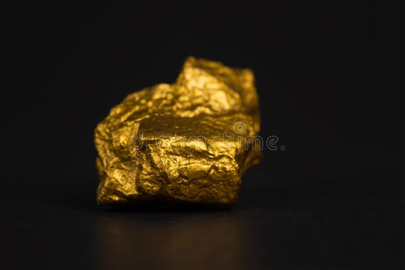 Closeup of gold nugget or gold ore on black background, precious. Stone or lump of golden stone, financial and business concept idea stock image