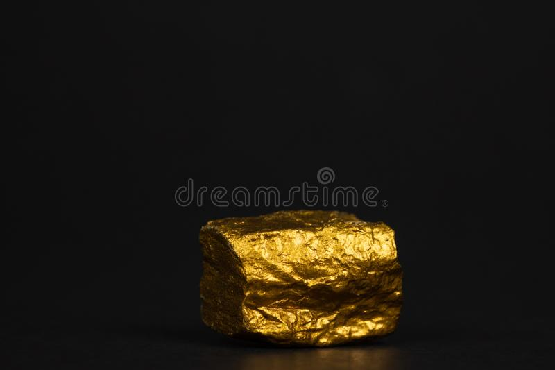Closeup of gold nugget or gold ore on black background, precious. Stone or lump of golden stone, financial and business concept idea stock photography