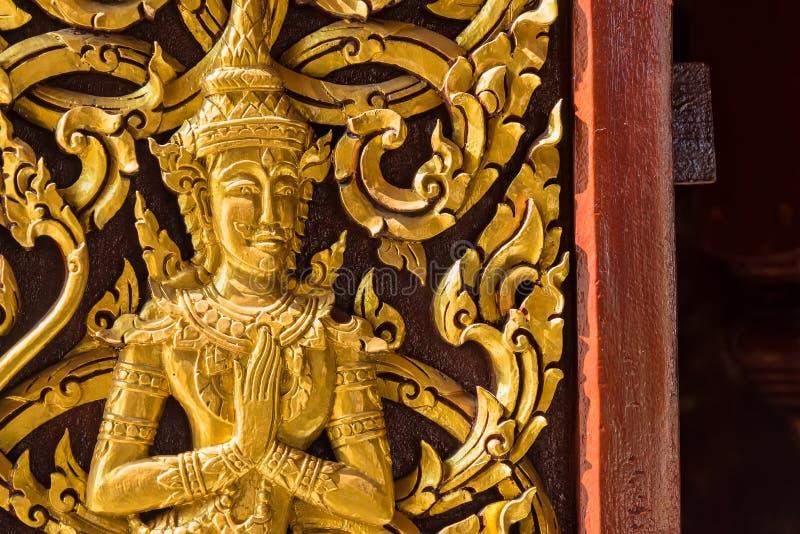 Closeup Golden Deva Carve an der Tür, Tempel in Thailand lizenzfreie stockbilder