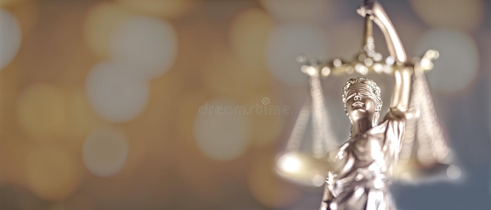 Statue Of Lady Justice. Closeup of golden lady Justice statue - focus on foreground with bokeh background royalty free stock photography