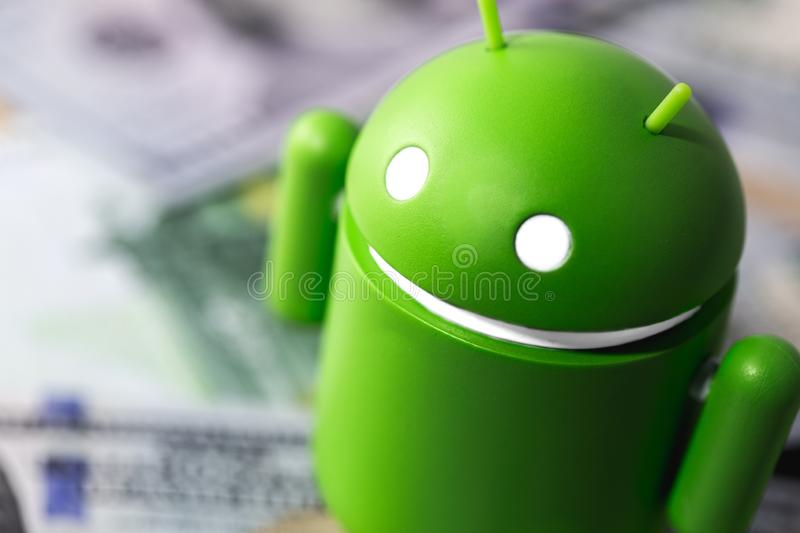 Google Android figure standing on money royalty free stock images