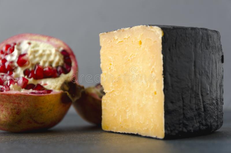 Closeup of gouda cheese and ripe pomegranate on dark table.Fruits and cheeses stock photo