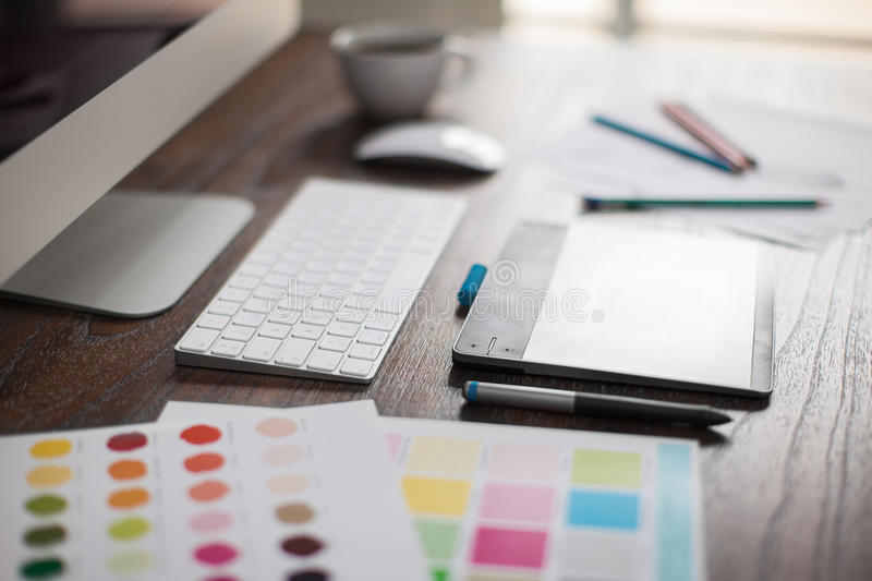 Closeup of a graphic designer's desk. Shallow depth of field closeup of a graphic designer's workspace with a pen tablet, a computer and some color swatches stock images