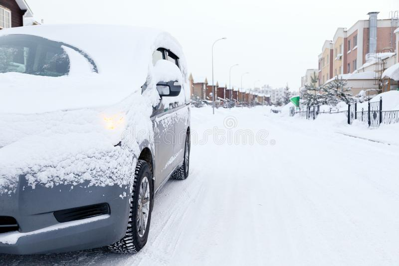 Closeup gray minibus dirty car covered with snow on city background. Front view. Concept snowy weather, fall, bad northern weather royalty free stock photography