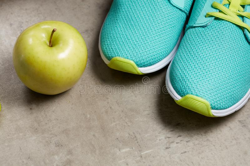 Closeup on green apple and sneakers on floor stock image