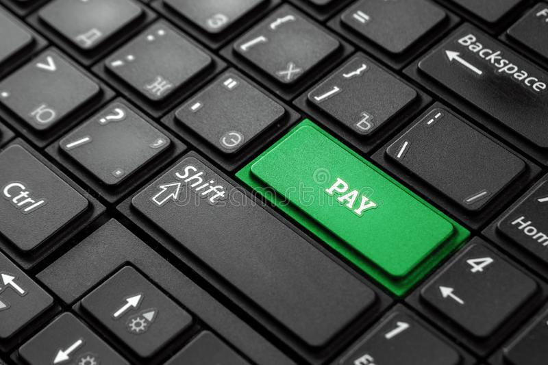 Closeup of a green button with the word pay, on a black keyboard. Creative background, copy space. Concept magic button royalty free stock photo