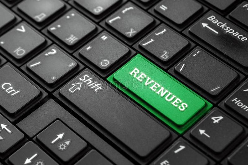 Closeup of a green button with the word revenues,on a black keyboard.Creative background,copy space.Concept magic button stock image