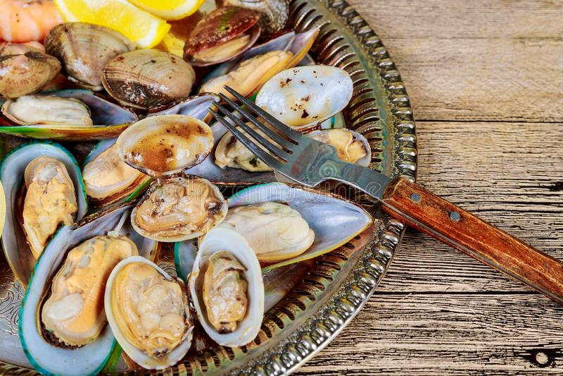 Closeup of green mussels and lemon in selective focus, studio shot royalty free stock image