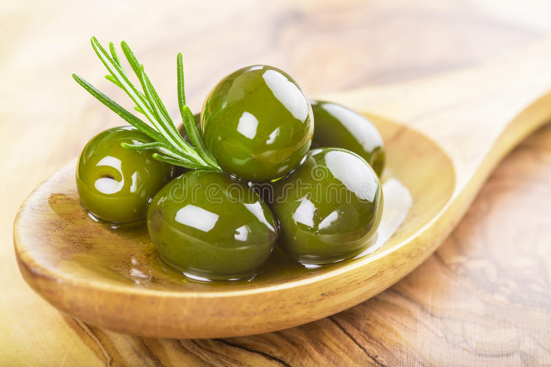 Closeup from green olives with oil on a wooden spoon stock photography