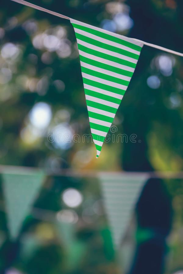 Closeup of a green striped flag on a white rope in the park royalty free stock photo